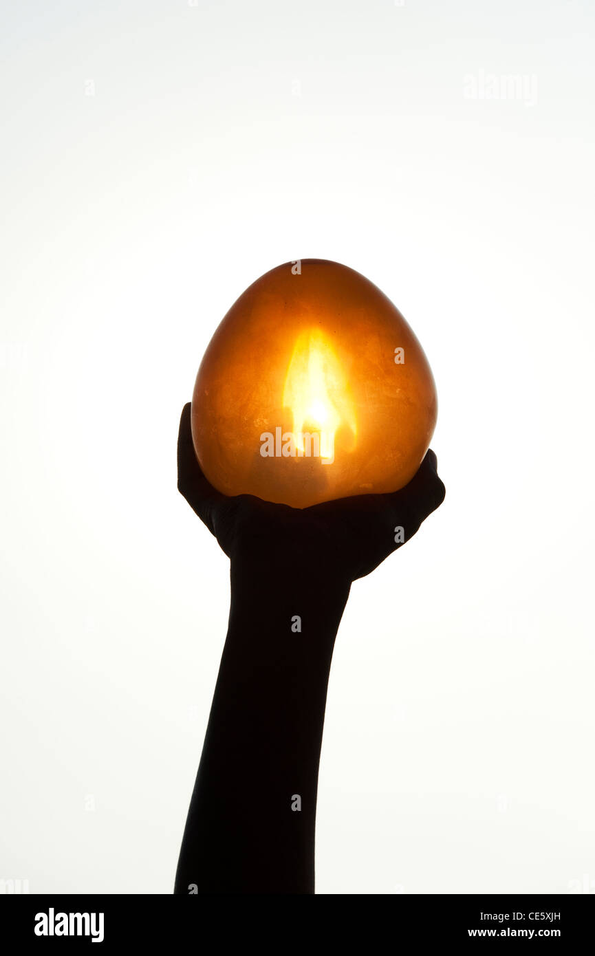 Silhouette hand holding a round water balloon in front of the sun giving the illusion of a candle flame. India - Stock Image