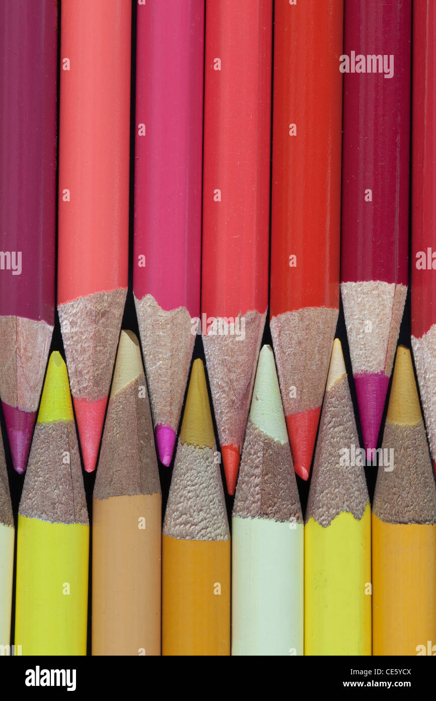Colored Pencils - shades of reds; golds and yellows; pink - Stock Image