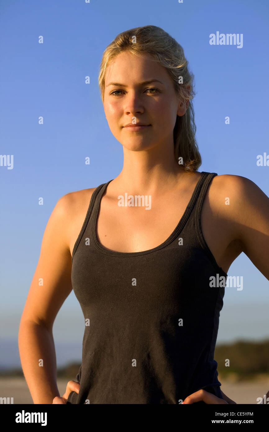Athletic young woman close-up against blue sky - Stock Image