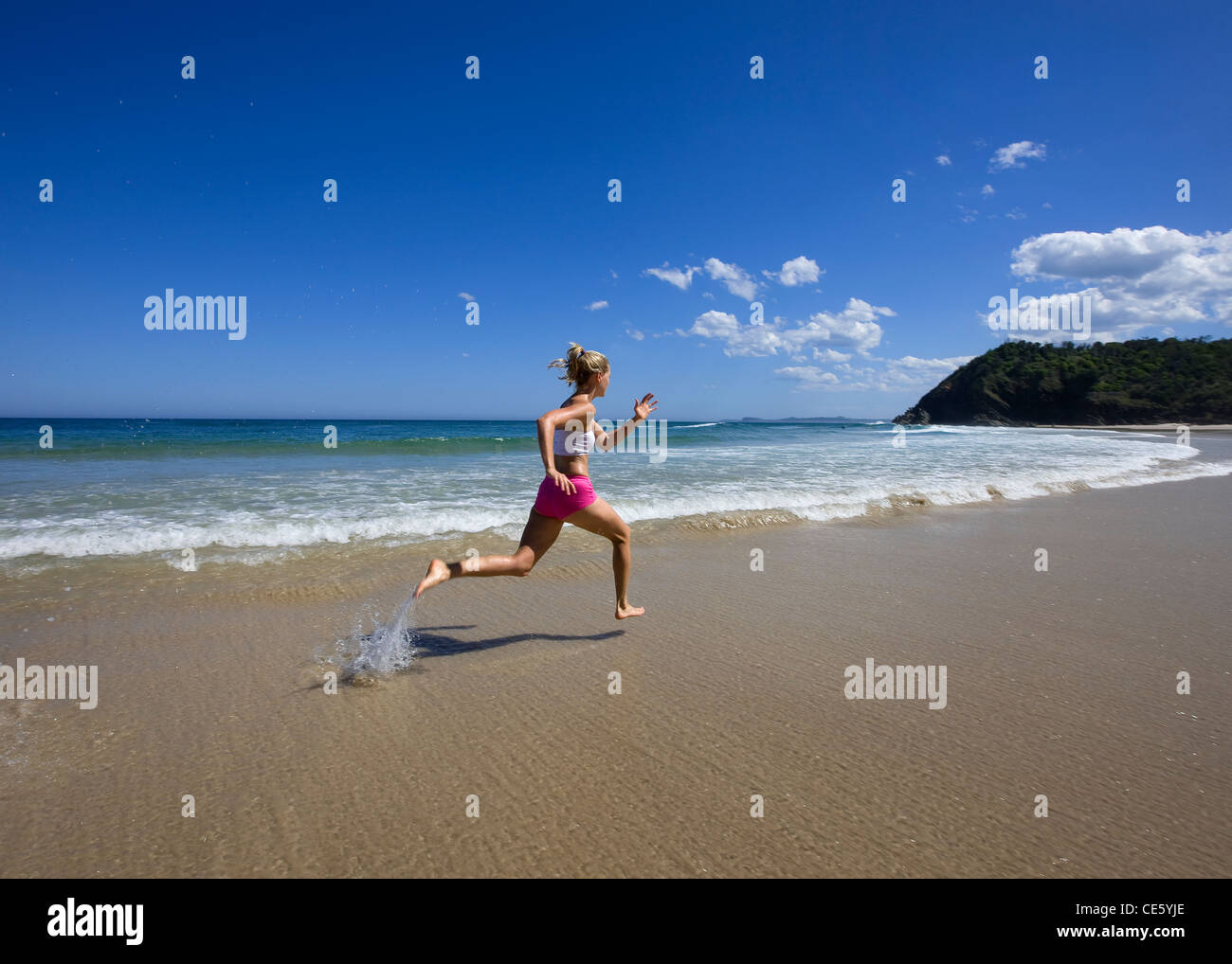 Girl doing a training session on the beach - Stock Image