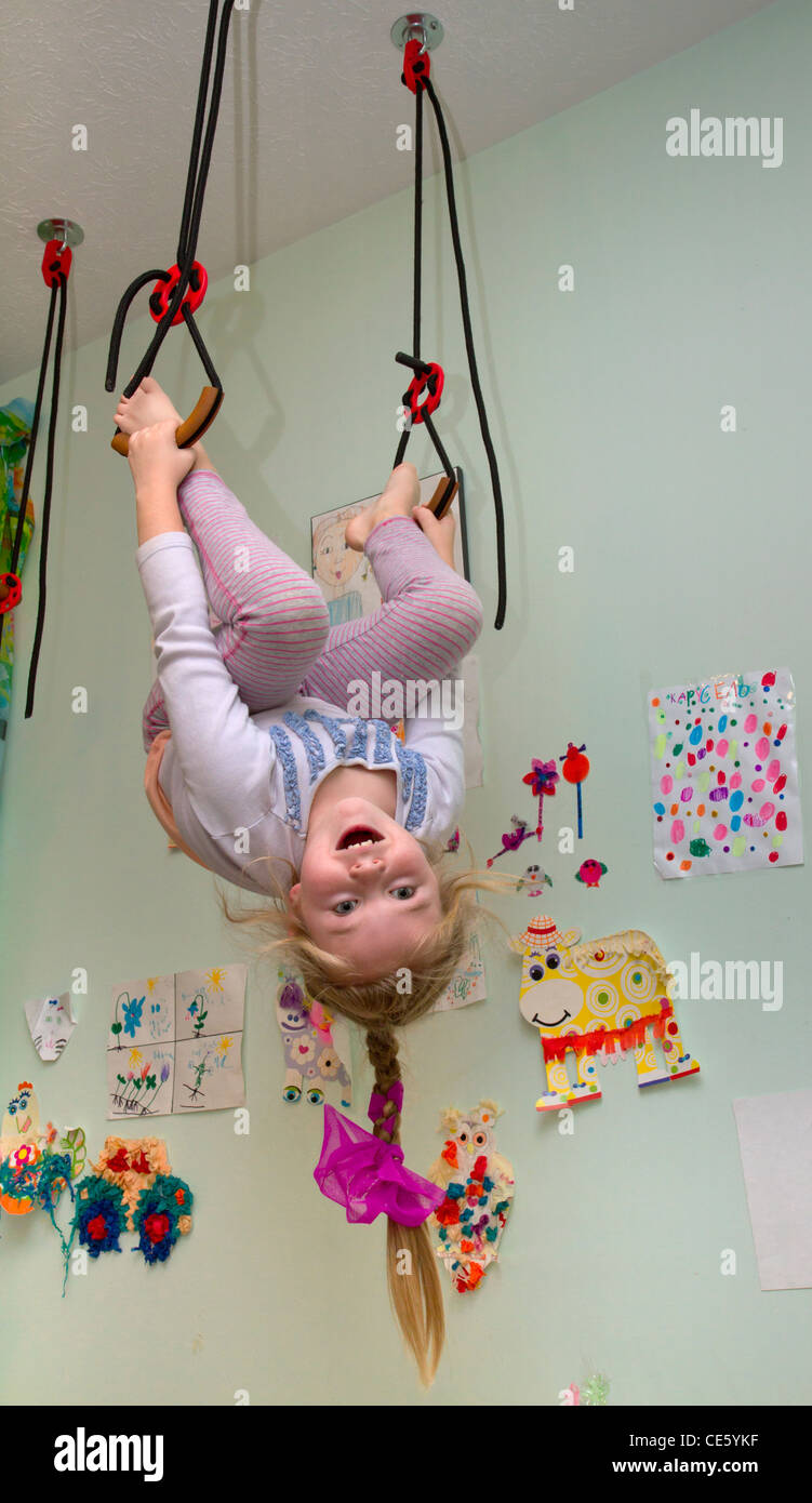 A 7-years old girl hanging on gymnastic rings in her home room. - Stock Image