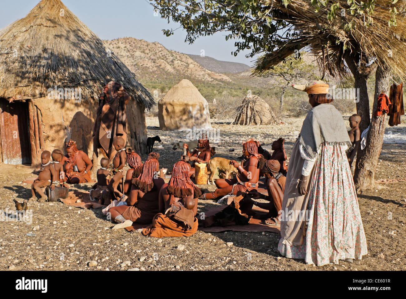 Herero woman and Himba people in Himba village near Opuwo, Namibia - Stock Image