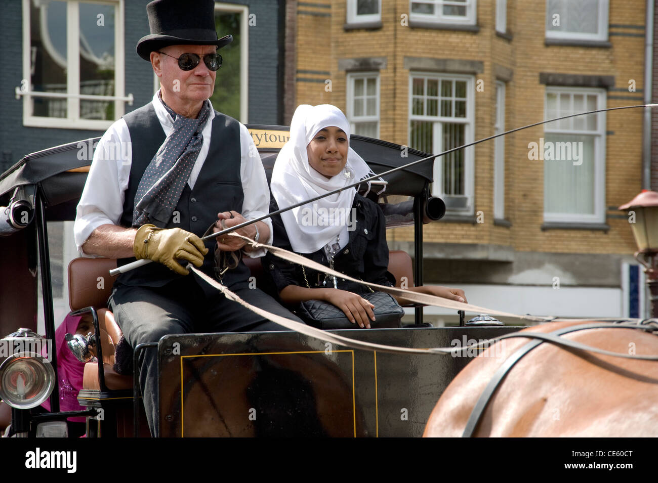 Carriage and horse carrying tourist at Amsterdam prinsengracht. - Stock Image