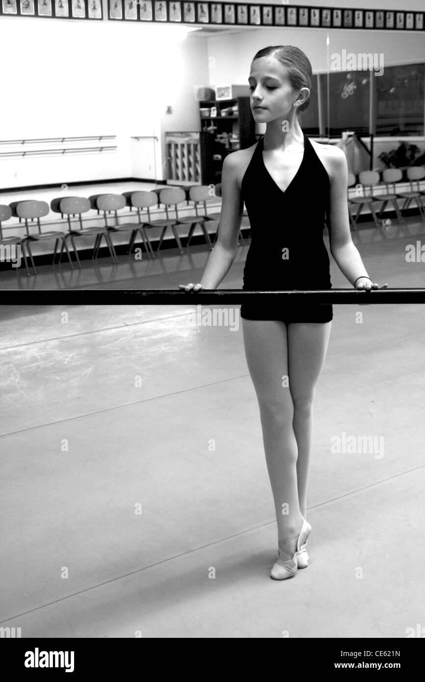 Girl practicing pointe holding balle bar at ballet studio Stock Photo