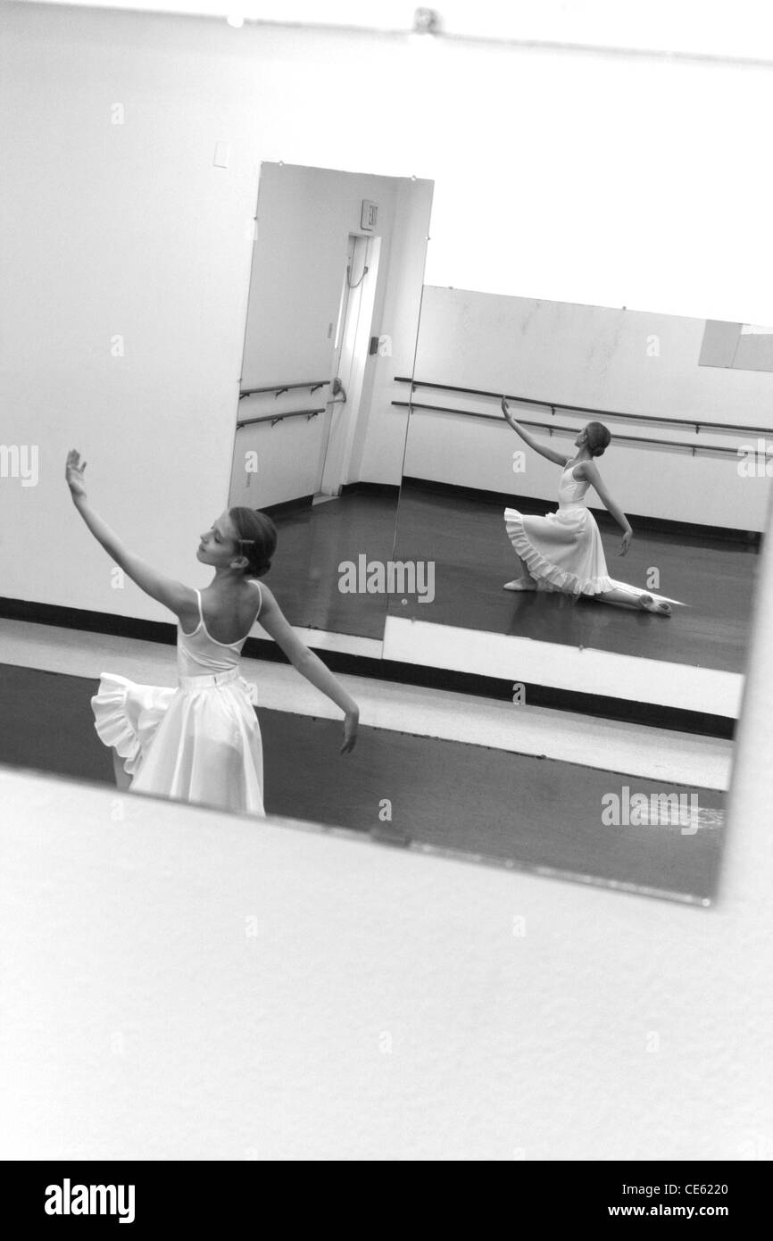 Mirror image of young female ballerina practicing in ballet studio Stock Photo