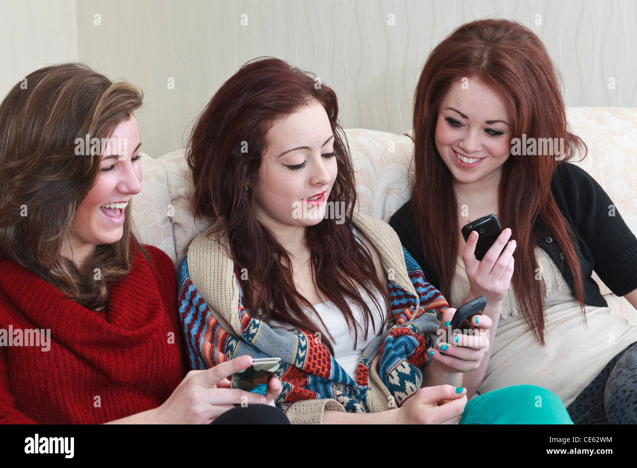 Three generation z teenage girl friends aged 15 years having a laugh looking at photos on a mobile phone whilst - Stock Image