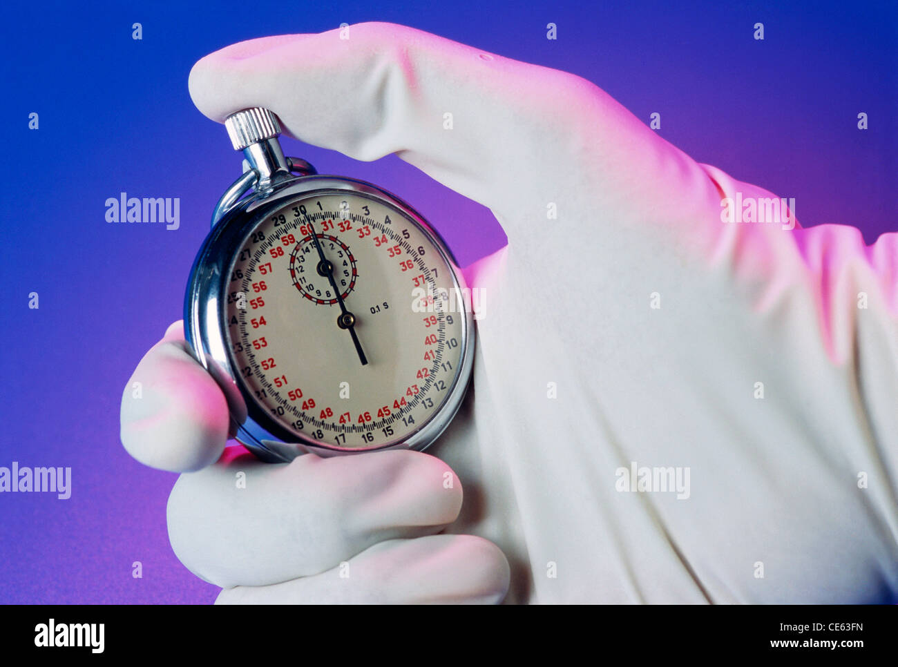 Hand wearing white glove holding stopwatch timer - Stock Image