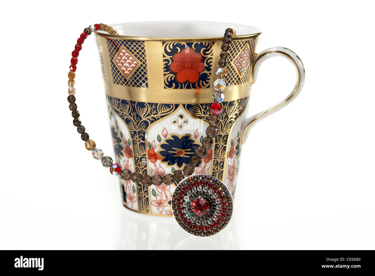 Fine bone china luxurious tea cup with jewellery over white background - Stock Image
