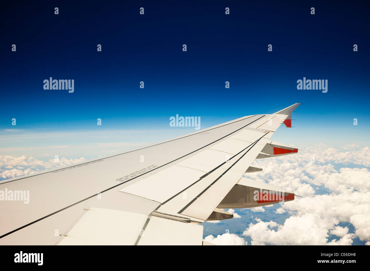View of jet aircraft wing above the clouds. Stock Photo