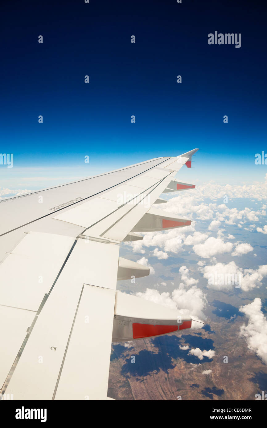 View of jet aircraft wing above the clouds. - Stock Image