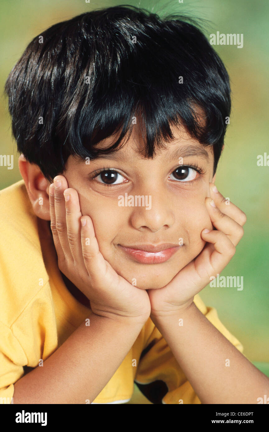 small young Indian boy face between both hands India   MR#152 - Stock Image