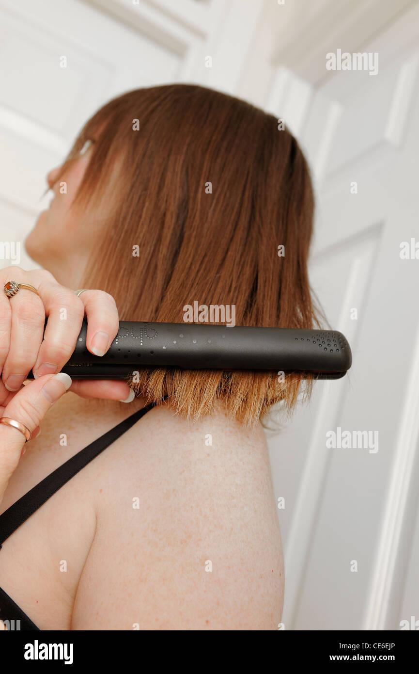 45 year old female using hair straighteners england uk - Stock Image