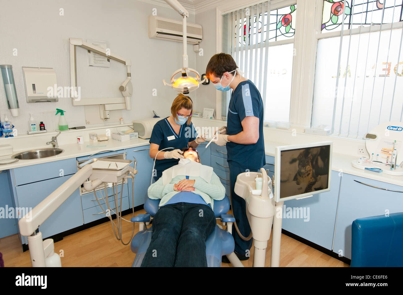 dental hygenist cleaning teeth chair dentist clean hygene checking check up female girl caucasian white check up - Stock Image