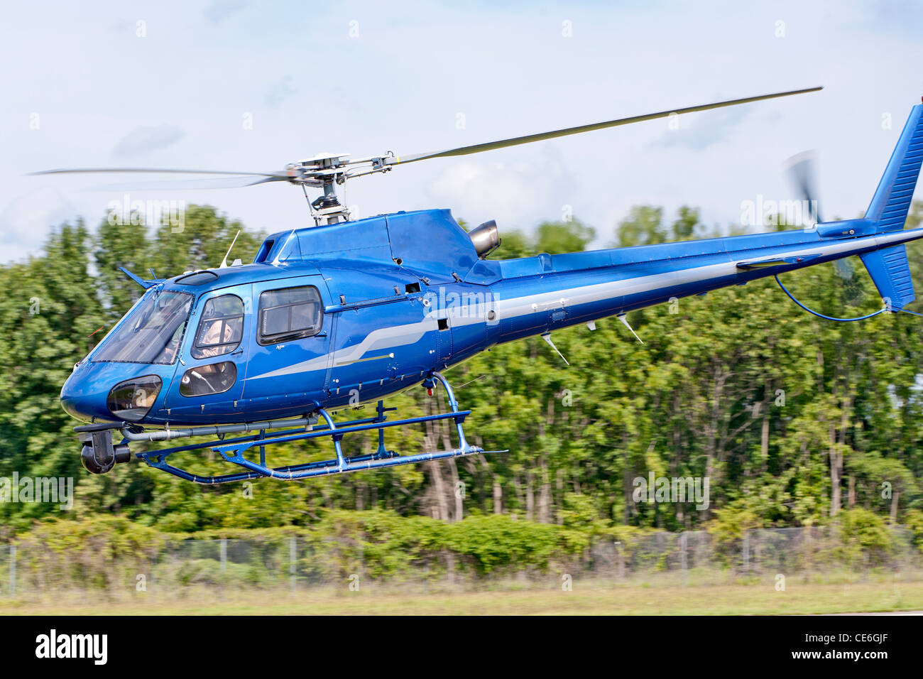 A Eurocopter Rotorcraft helicopter flies low to the ground. - Stock Image