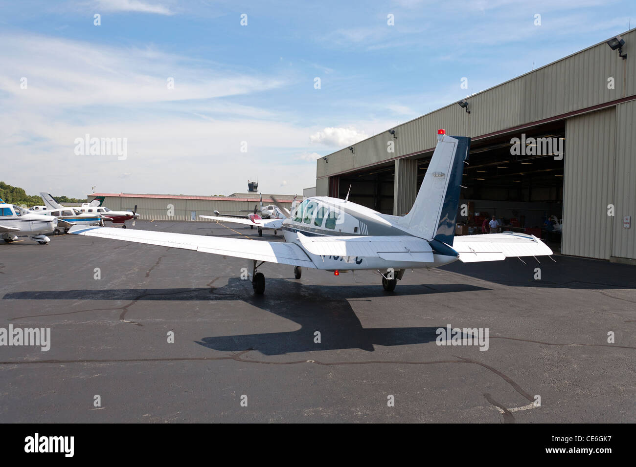 A group of airplanes sit on the ground outside an airplane hanger. - Stock Image