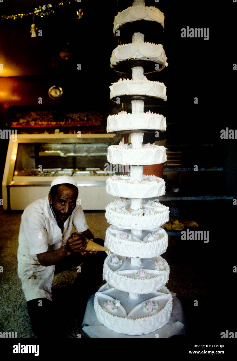 Cake maker decorates multi tiered wedding cake at bakery in Baghdad