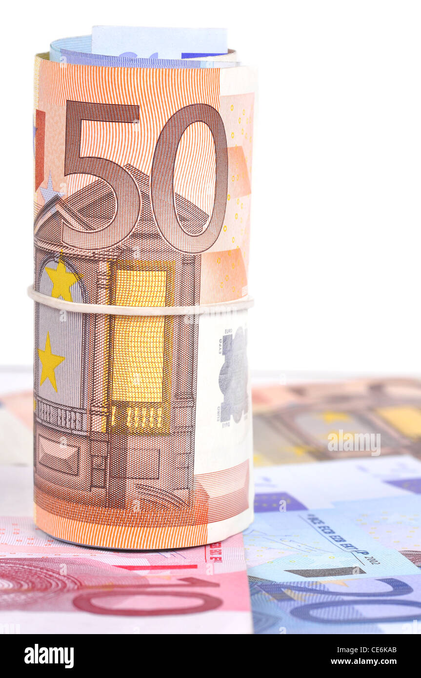 Roll of euro bank notes on top of some more notes - Stock Image