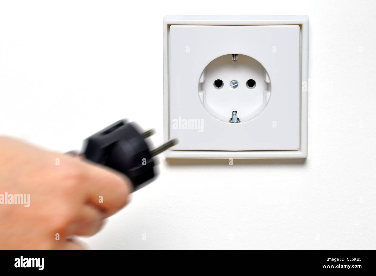 Hand connecting a plug to a socket - Stock Image