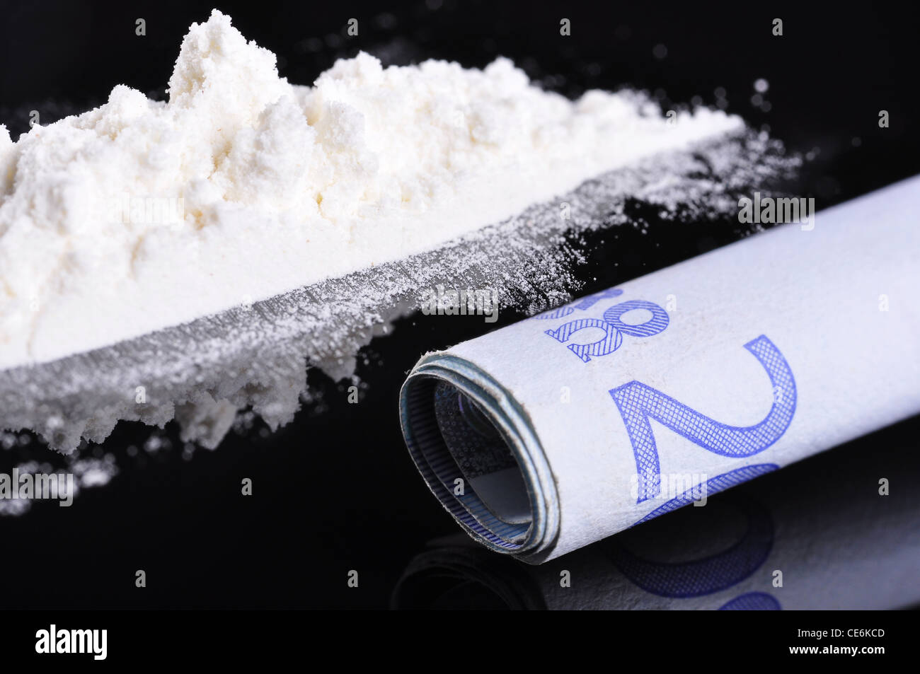 A bank note next to a line of cocaine, ready to be snorted - Stock Image