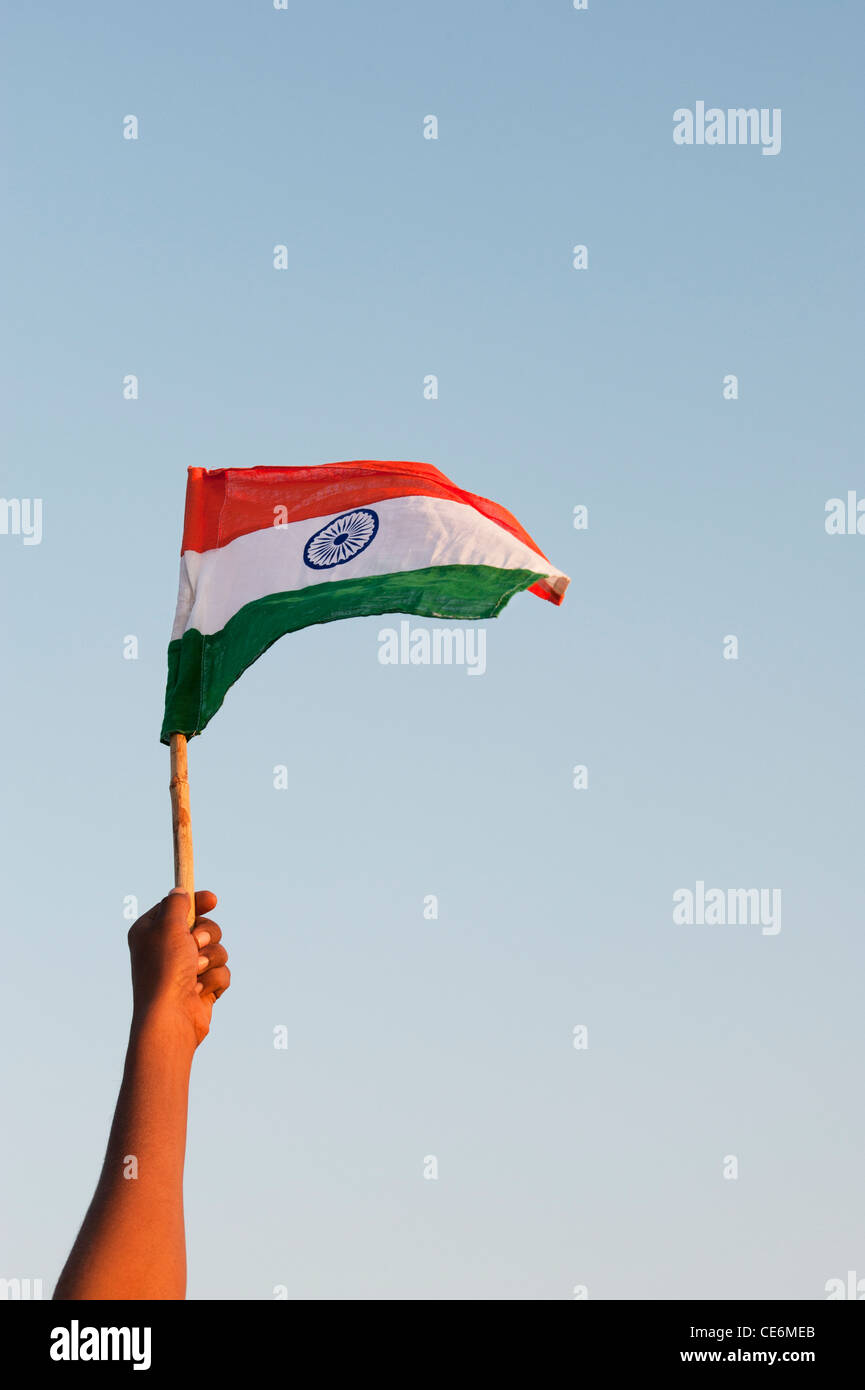 Indian mans hands holding an Indian flag against a blue sky. India - Stock Image