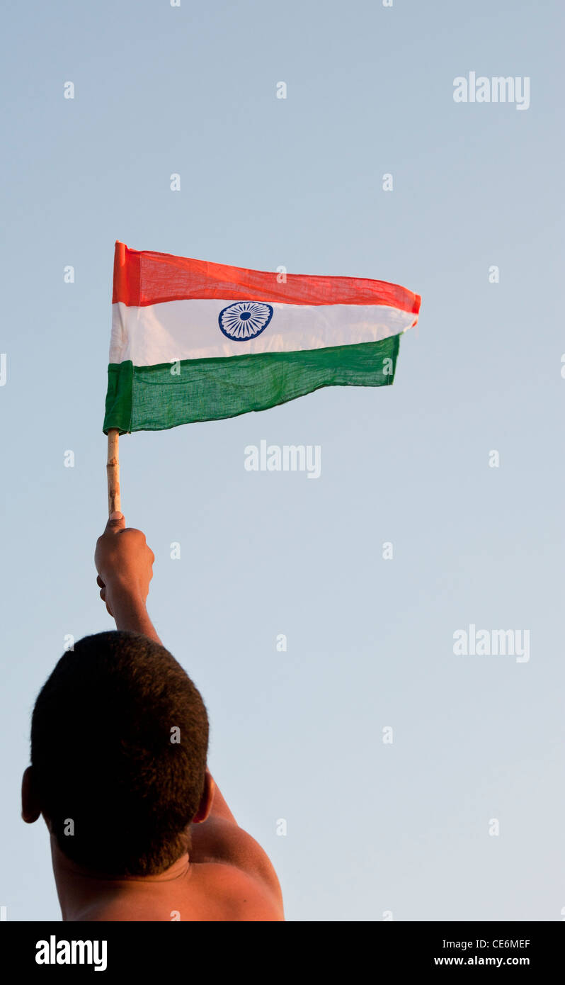Indian man holding an Indian flag against a blue sky. India - Stock Image