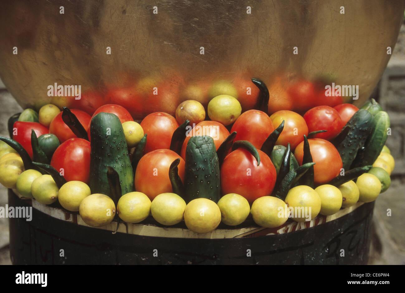 Indian snack fastfood items red tomato yellow lemon green cucumber green chilly ; Shimla ; himachal pradesh ; india - Stock Image