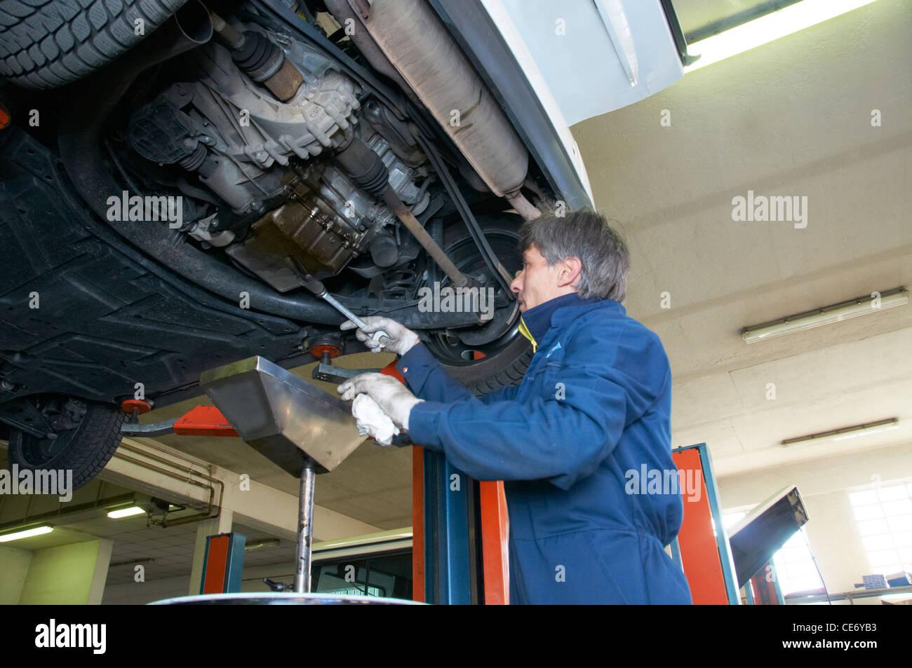 mechanic repairs a car in a garage - Stock Image
