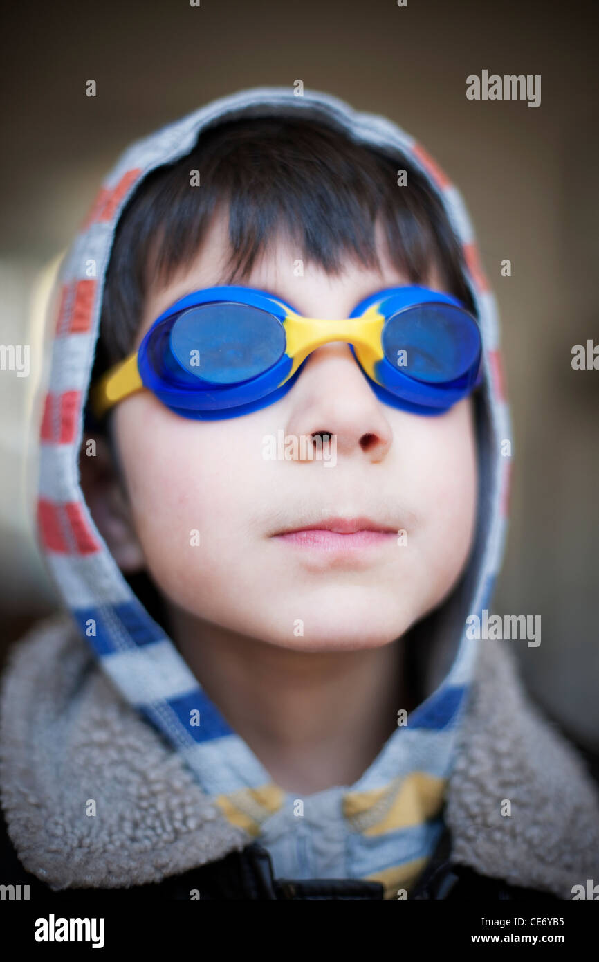 Boy wearing blue swimming goggles and hood - Stock Image