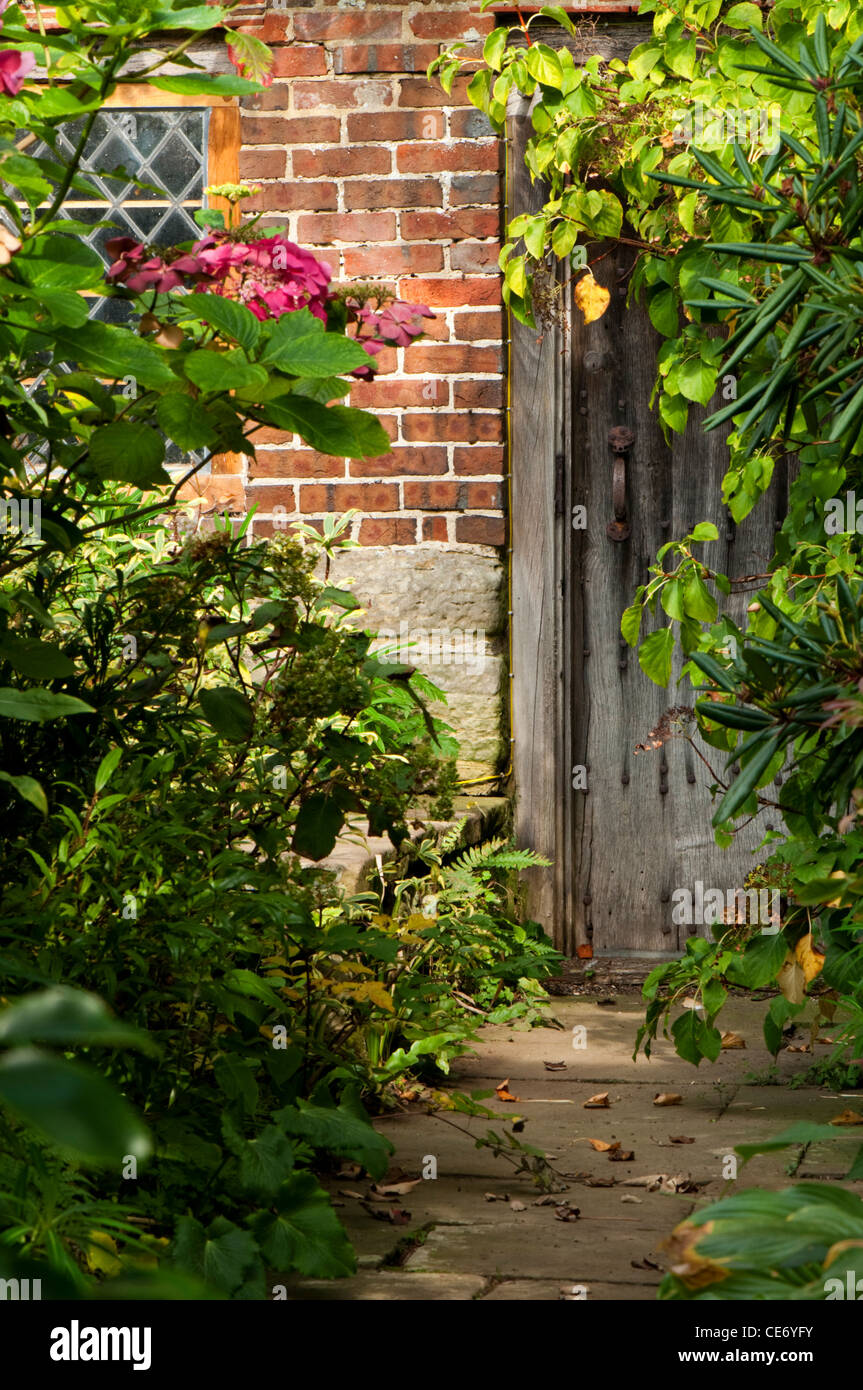 An over grown pathway leading to an old wooden door. - Stock Image