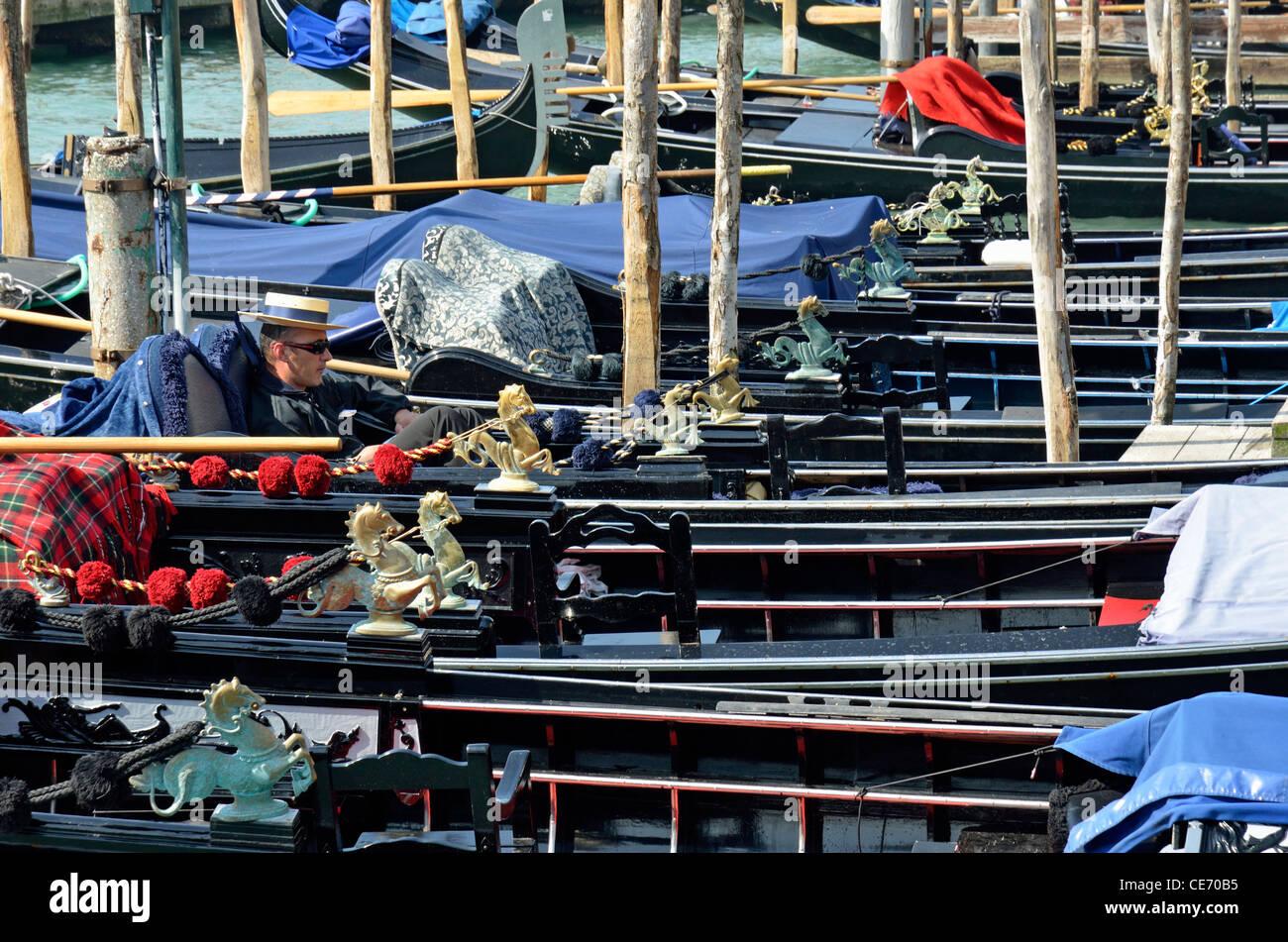 Gondolier resting in moored gondola, Venice, Italy - Stock Image