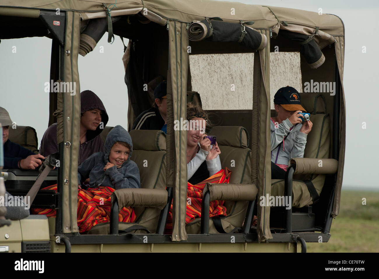 On-lookers on Safari enjoying the sighting of wild animals, Serengeti, Tanzania - Stock Image