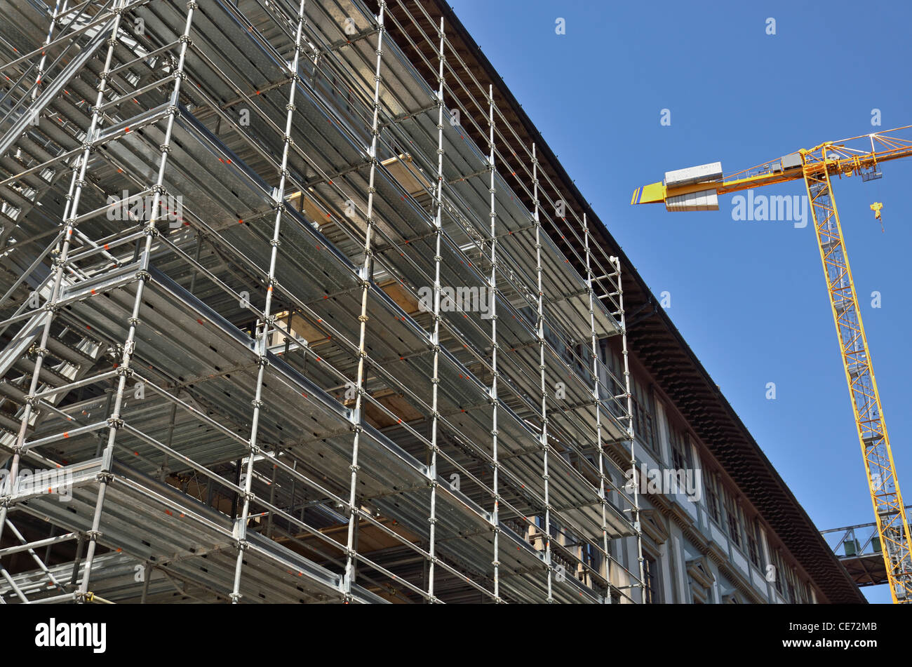 Construction crame by building and scaffolding, Florence, Tuscany, Italy - Stock Image