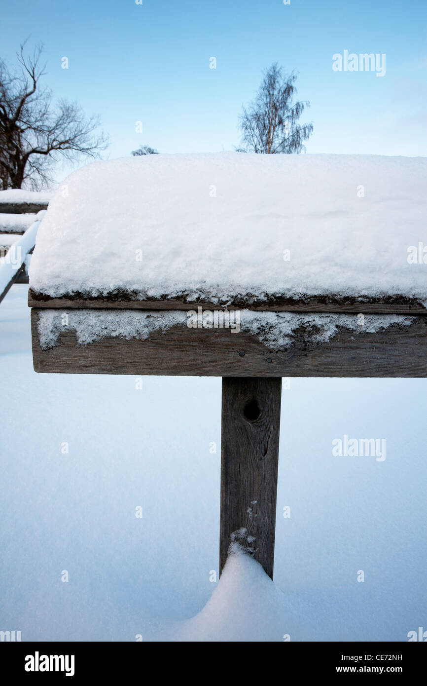 weathered old wooden handrail in snow, Finland - Stock Image