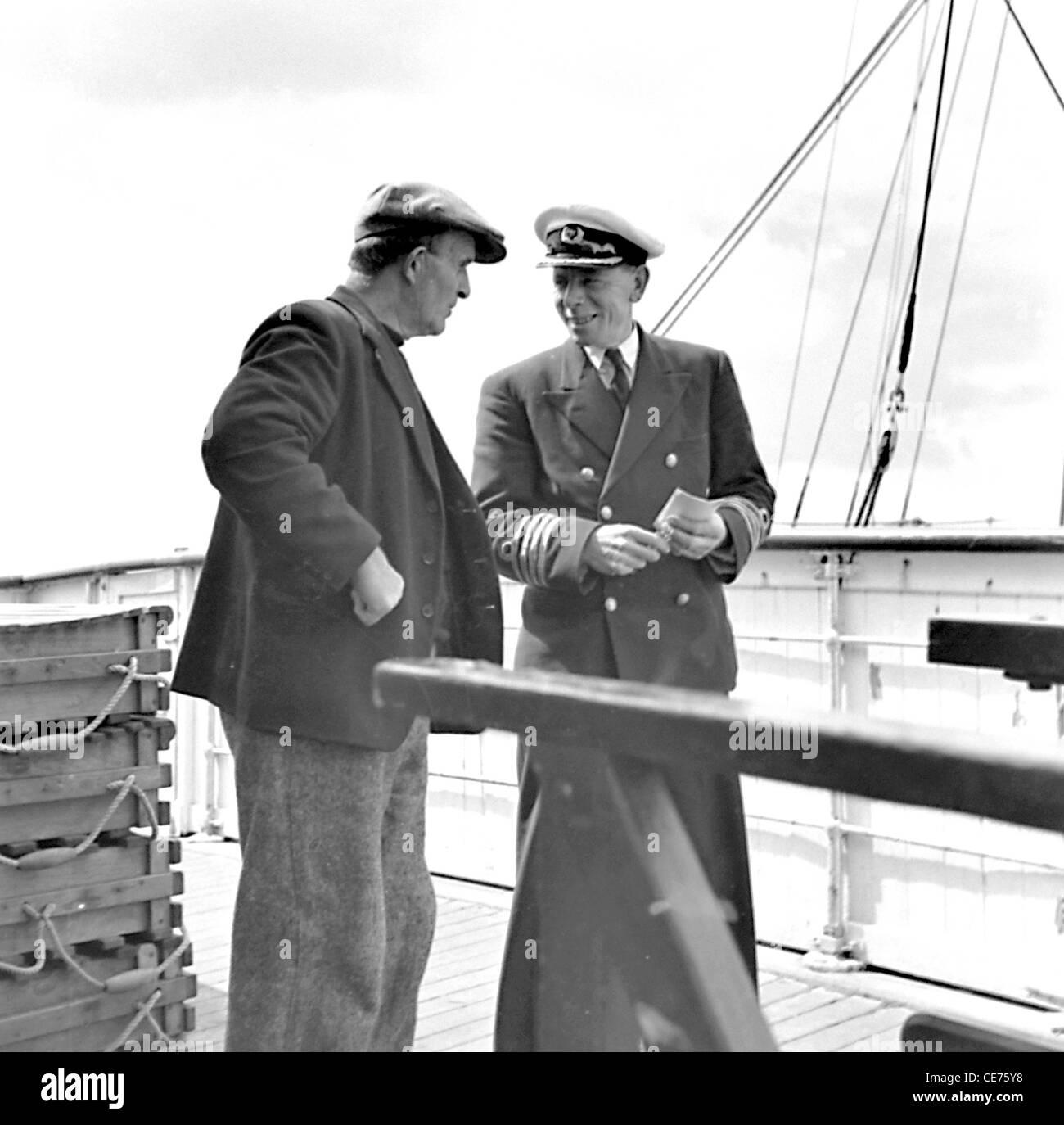 Islander Pat Hernon chats with Dun Angus skipper while docked at Kilronan pier Inis Mor  Aran Islands Co Galway - Stock Image
