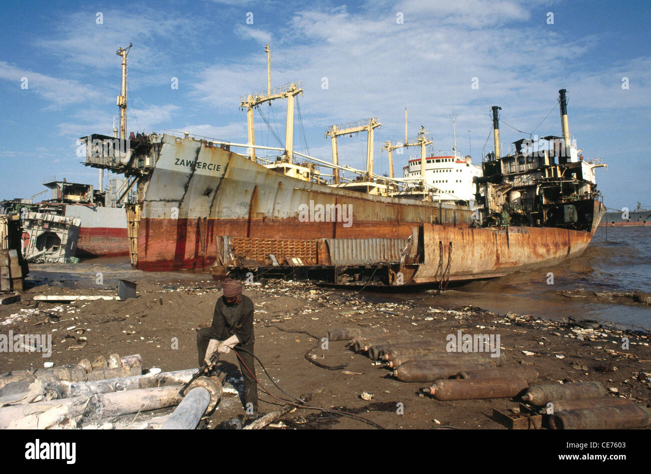 indian man gas cutting steel plate in alang ship breaking scrap yard