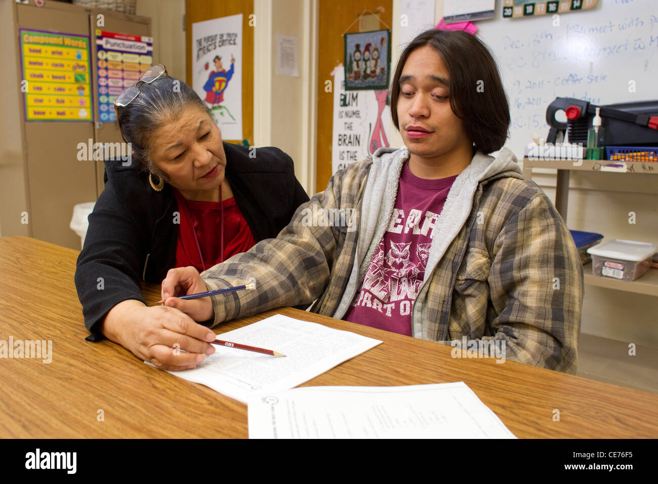 Hispanic female teacher in class works one-on-one with autistic teenage high school students - Stock Image