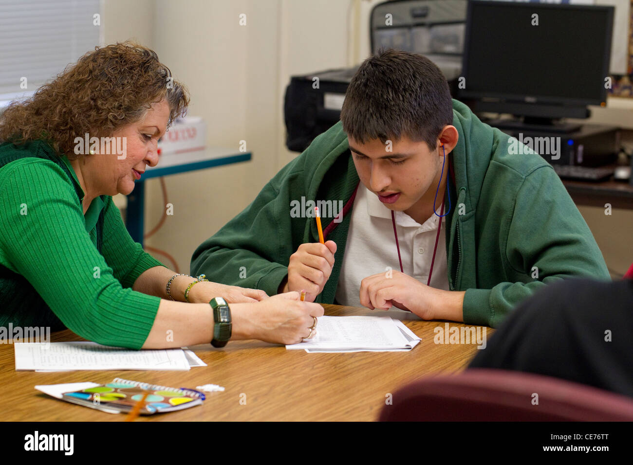 Anglo female teacher in class works one-on-one with autistic teenage Hispanic high school student - Stock Image