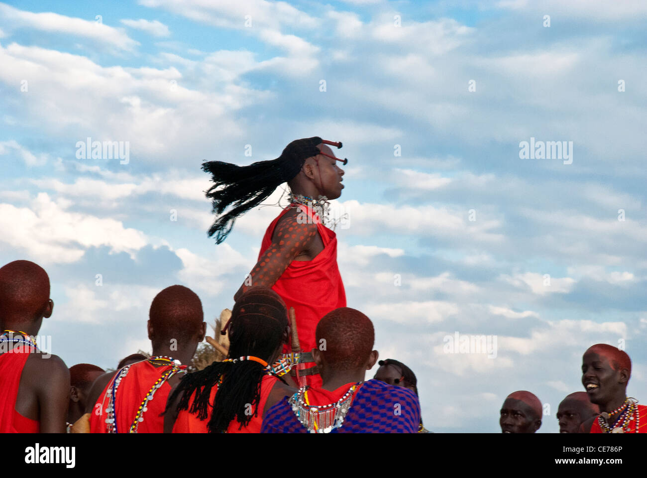 Masai men, doing a jumping dance, wearing traditional dress, in a village in the Masai Mara, Kenya, AfricaStock Photo