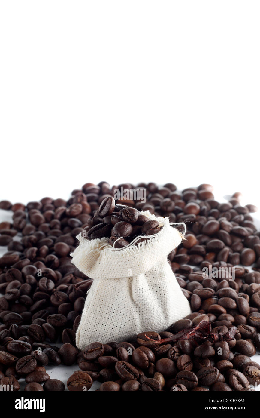 Coffee beans in a sack with a lot of beans around it - Stock Image
