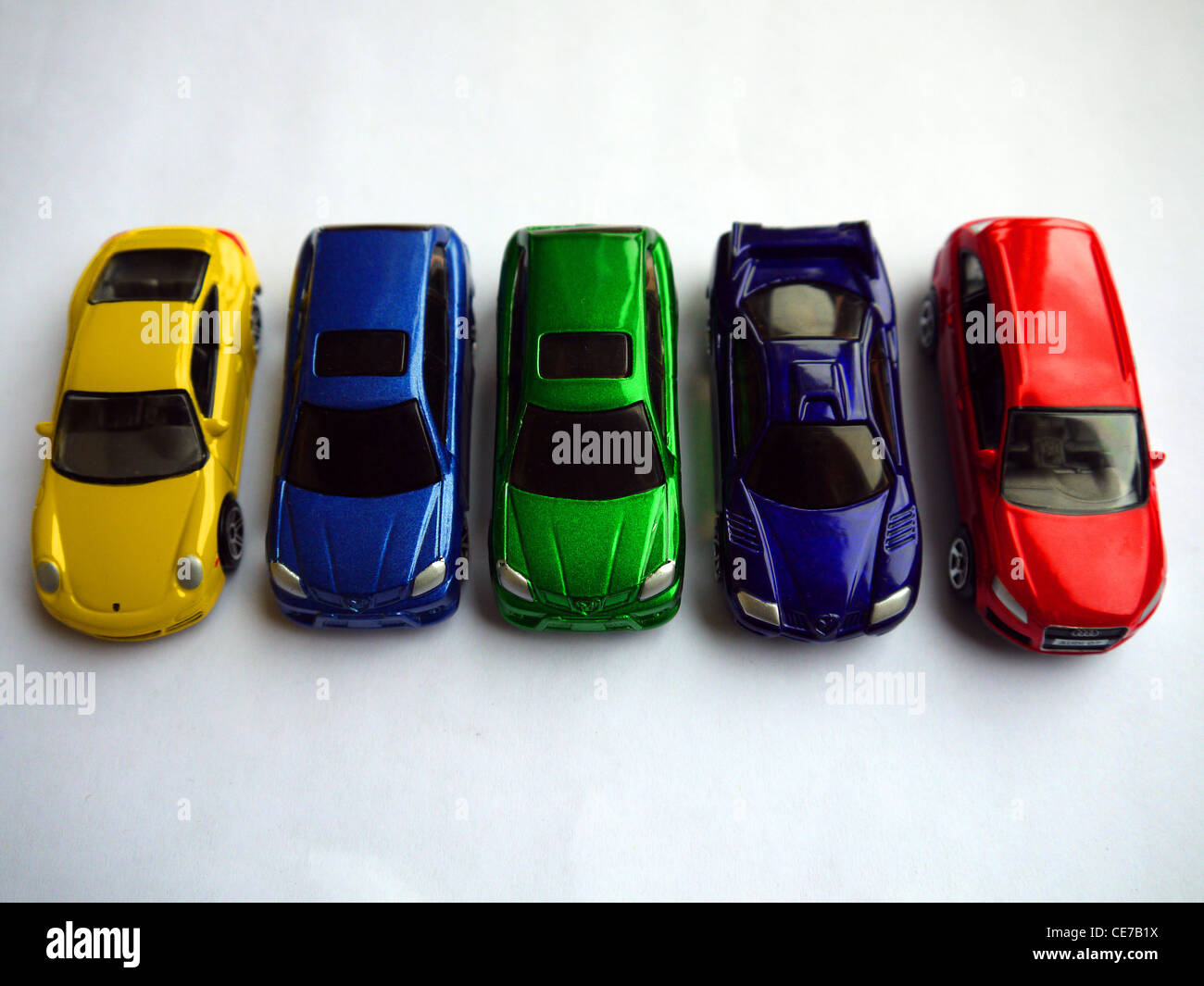 5 Toy Cars In A Row Yellow Blue Green Purple And Red Stock Photo