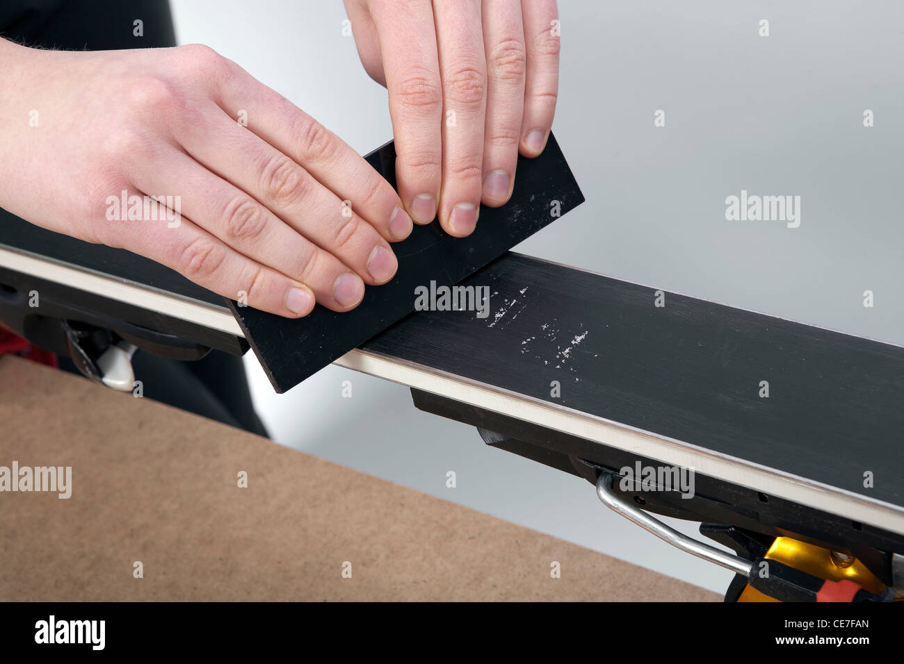 removing excess wax from race ski base with plastic scraper - Stock Image