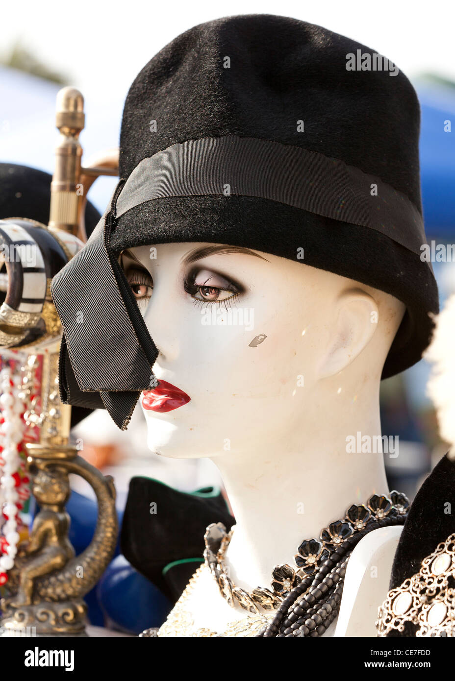 Female mannequin heads wearing hats at flea market - Stock Image