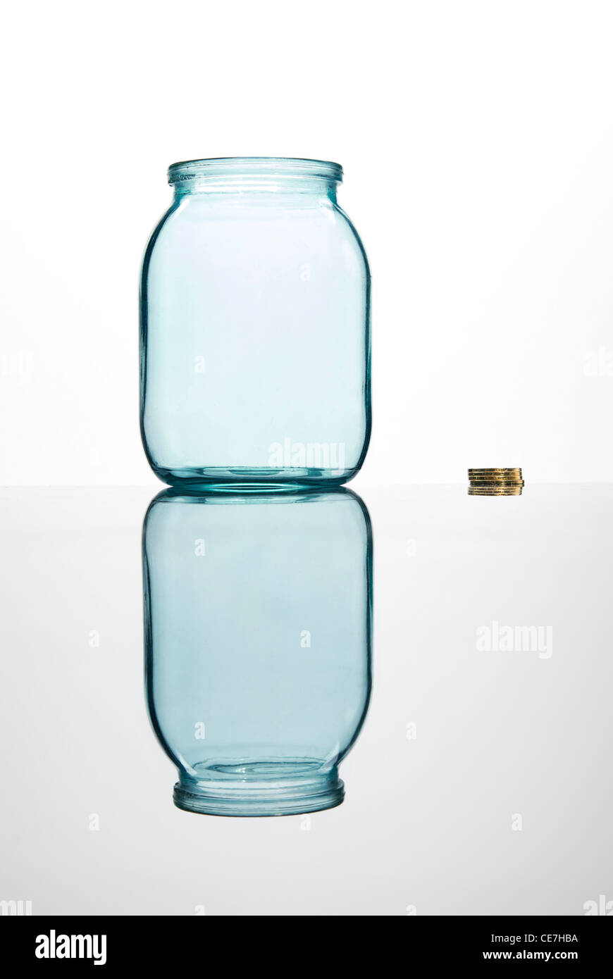 Coins and empty glass jar on white background Stock Photo