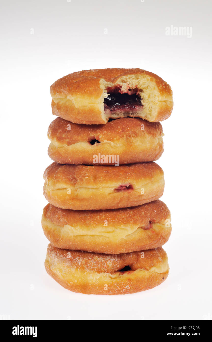 Stack of jelly donuts with bite taken out of top donut on white background cutout. - Stock Image