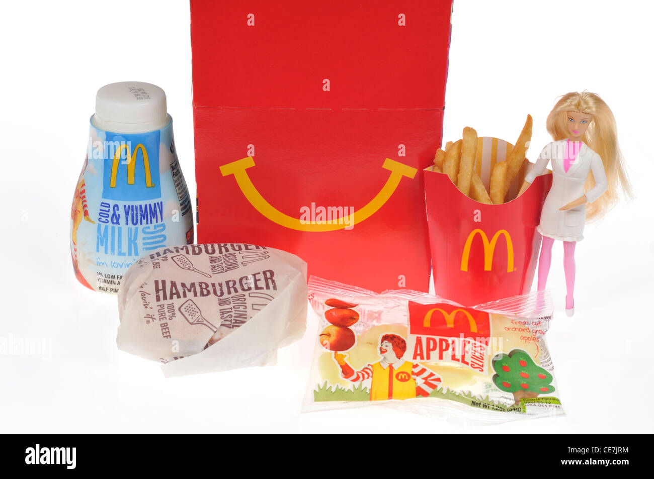 McDoanld's Happy Meal with a hamburger, french fries, milk and apple dippers and a Barbie doll toy on white - Stock Image