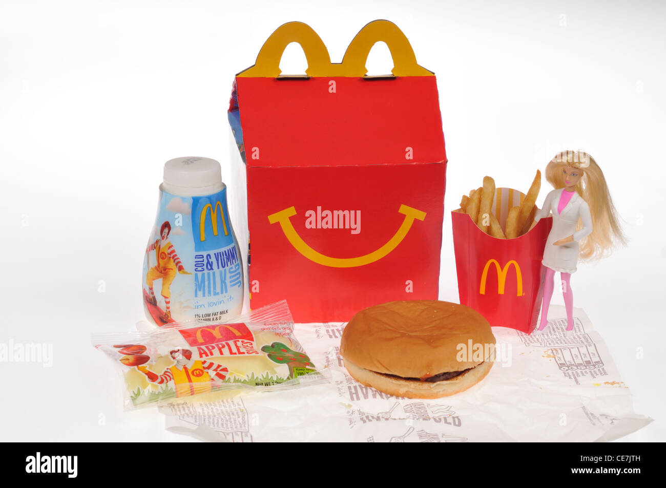 McDonald's Happy meal box with a burger, chips, milk and apple dippers  and a Barbie doll toy on white background - Stock Image
