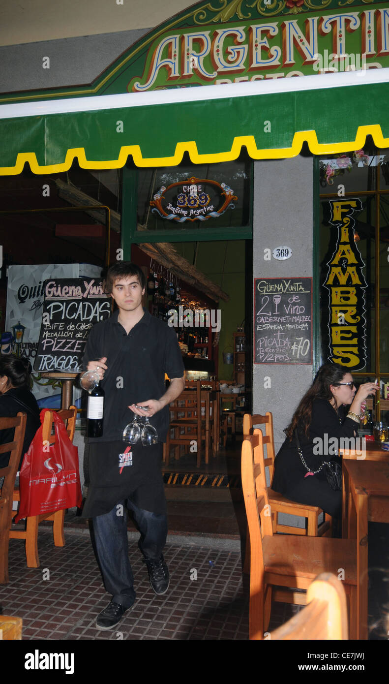 Waiter bringing wine at traditional steakhouse (parrilla) in San Telmo, Buenos Aires, Argentina. No MR or PR - Stock Image