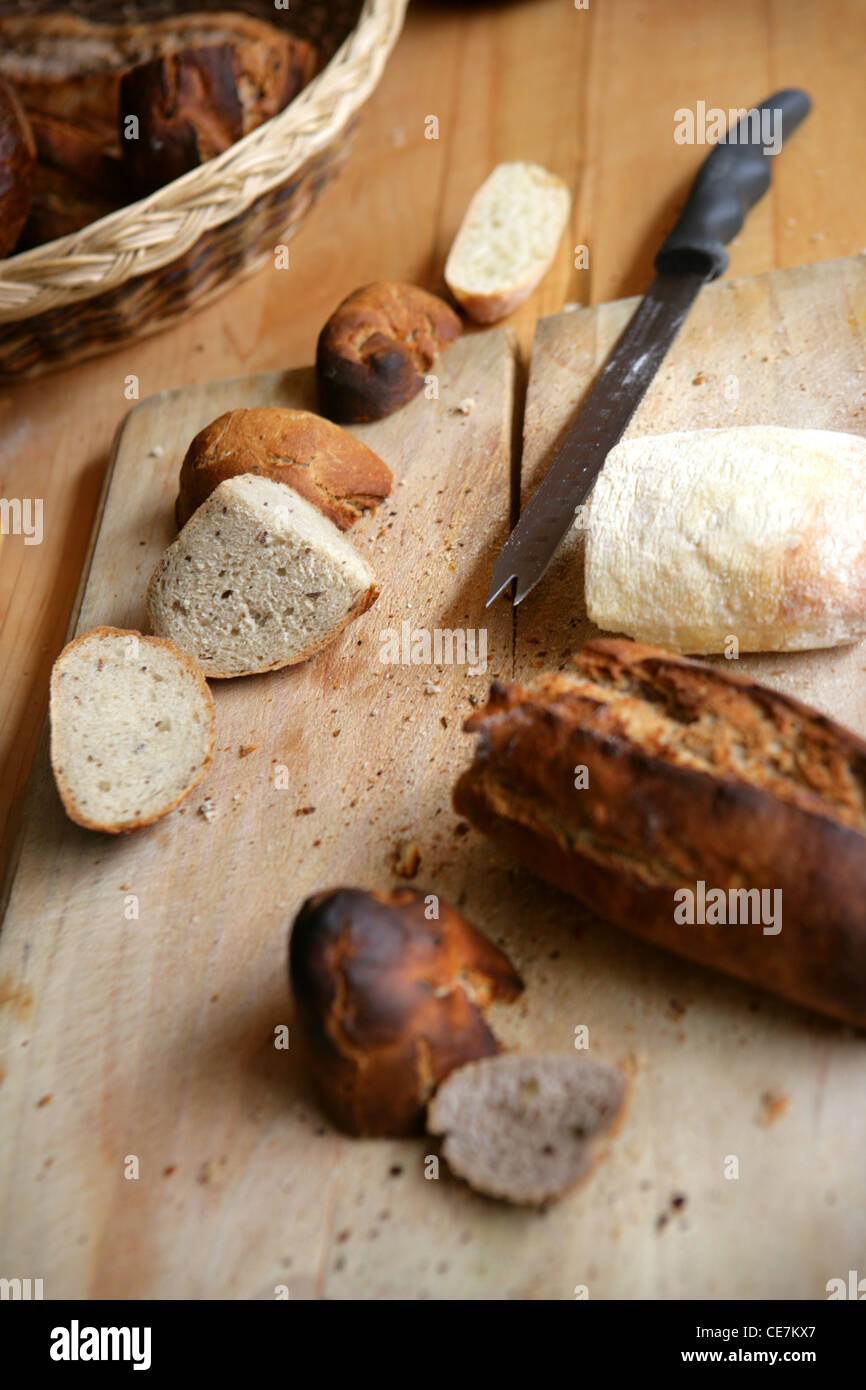 FRESH HOMEMADE BREAD ON A WOODEN CHOPPING BAORD - Stock Image