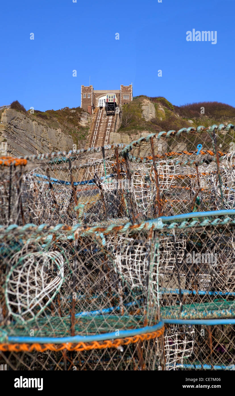 Fishing industry in Hastings in England with funicular lift in background and lobster pots - Stock Image