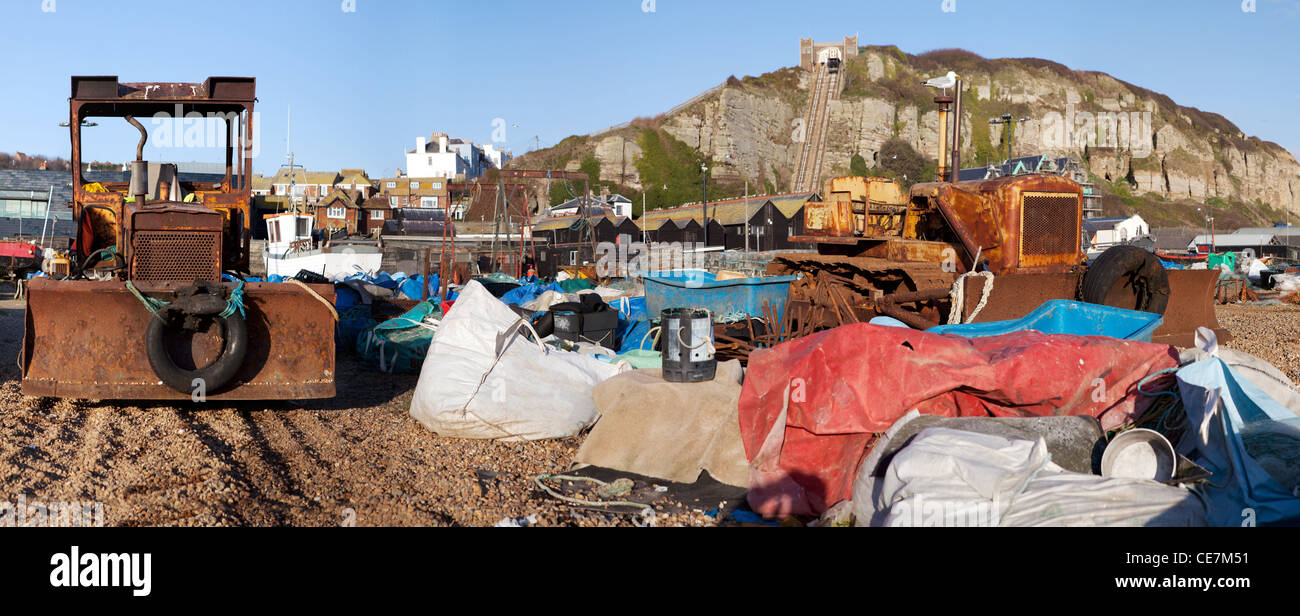 Fishing industry on beach in Hastings. Tractor or digger with agriculture equipment and town in background - Stock Image
